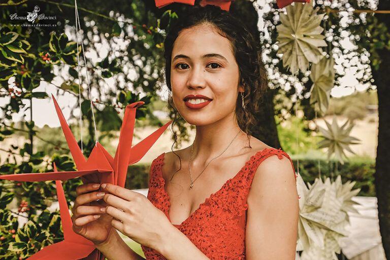 Una novia vestida de rojo en la finca donde celebra su boda, mantiene en sus manos una pajarita de papel roja